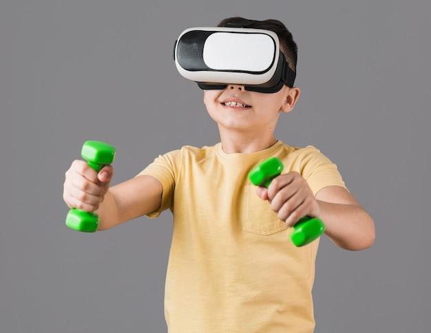Vue de face d'un garçon tenant des poids tout en portant un casque de réalité virtuelle
