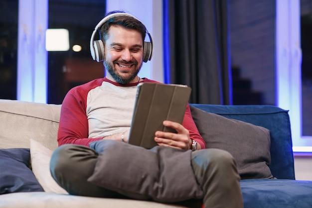 Vue de face d'un gars joyeux de 30 ans avec une barbe bien entretenue qui apprécie des chansons cool dans ses écouteurs et fait des mouvements de danse avec les mains