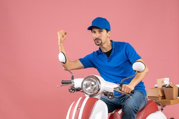 Vue de face d'un gars de messagerie émotionnel fier portant un chapeau assis sur un scooter sur fond de pêche pastel