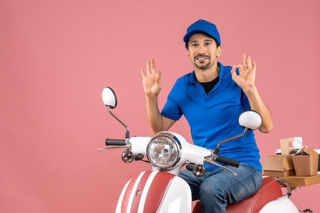 Vue de face d'un gars de messagerie heureux souriant portant un chapeau assis sur un scooter et faisant un geste de lunettes sur fond de pêche pastel