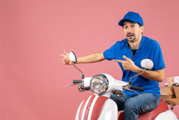 Vue de face d'un gars de messagerie plein d'espoir portant un chapeau assis sur un scooter sur fond de pêche pastel