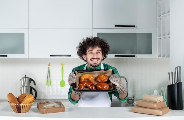 Vue de face d'un gars souriant portant un support montrant une pâtisserie fraîchement préparée dans la cuisine blanche