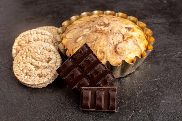 Une vue de face gâteau rond sucré délicieux délicieux à l'intérieur du moule à gâteau avec des barres de chocolat et des chips de pain sur le fond gris biscuit biscuit au sucre