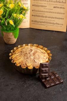 Une vue de face gâteau rond sucré délicieux délicieux à l'intérieur du moule à gâteau avec des barres de chocolat fleurs et notes de musique cahier sur le fond gris biscuit biscuit au sucre