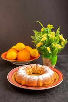 Une vue de face gâteau rond sucré avec du sucre en poudre en tranches de délicieux gâteau isolé sucré à l'intérieur de la plaque avec des citrons et des biscuits au sucre biscuit fond gris