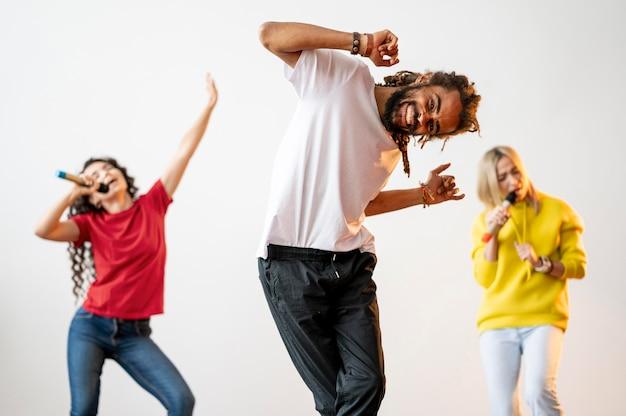 Vue de face des gens multiraciaux chantant et dansant ensemble