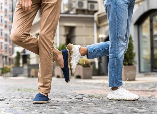 Vue de face, les gens saluent d'une nouvelle manière normale avec leurs pieds