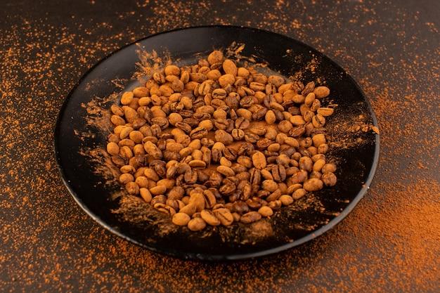 Une vue de face des graines de café brun à l'intérieur de la plaque noire