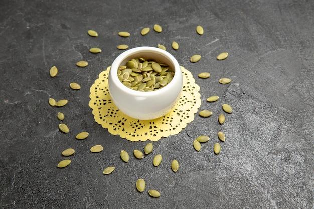 Vue de face graines de citrouille fraîches sur fond sombre couleur de la graine de nombreux granulés de citrouille