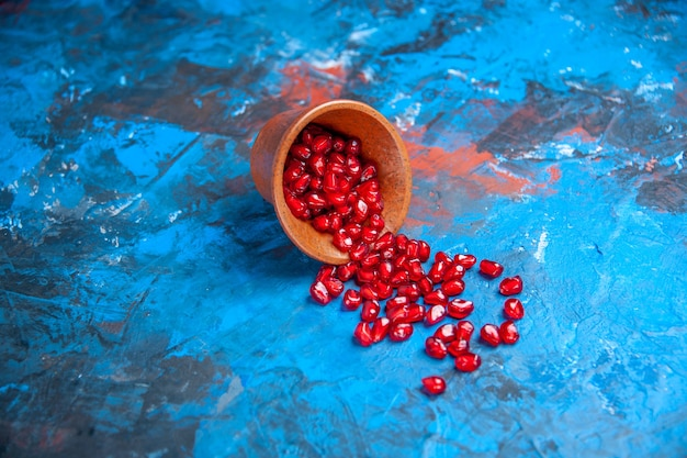 Vue de face des graines de grenade dans un petit bol en bois sur un endroit libre bleu