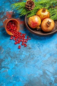 Vue de face des graines de grenade placées dans une tasse en bois avec des grenades à graines éparses sur une plaque en bois sur fond bleu espace libre
