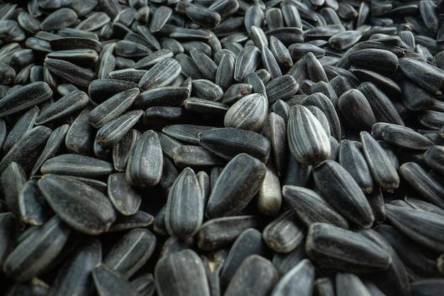 Vue de face graines de tournesol noires beaucoup d'huile de film de collation de noix