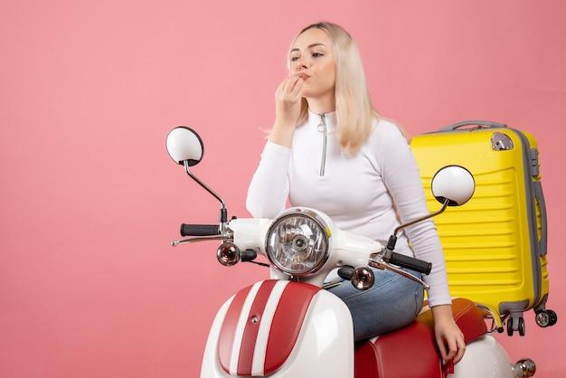 Vue de face gratifiée jeune femme sur cyclomoteur faisant signe savoureux