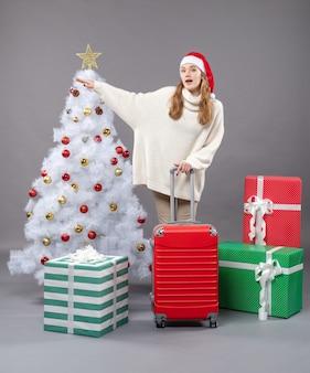 Vue de face grêlant fille avec bonnet de noel tenant valise rouge