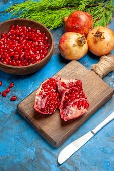 Vue de face une grenade coupée et un couteau de dîner sur une planche à découper des graines de grenade dans un bol et des grenades sur fond bleu