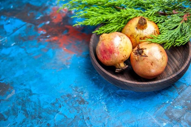 Vue de face grenades fraîches dans un bol en bois branche de pin sur bleu