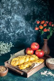 Vue de face de gressins torsadés pommes sur planche de bois rectangle avoine et grains de blé dans des bols
