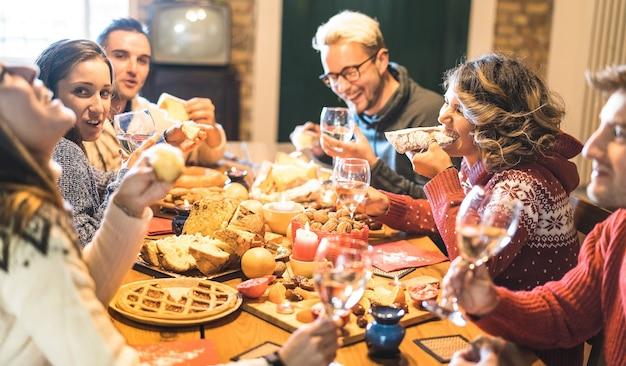 Vue de face d'un groupe d'amis dégustant des bonbons de noël et s'amusant à la maison