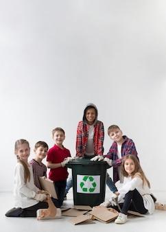 Vue de face groupe d'enfants posant recycler ensemble