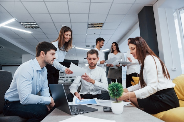 Vue de face. groupe de jeunes pigistes au bureau ont une conversation et souriant
