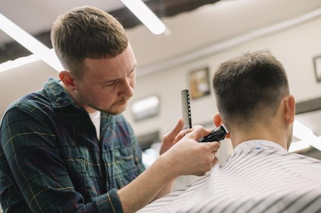 Vue de face de hairstilyst donnant une coupe de cheveux