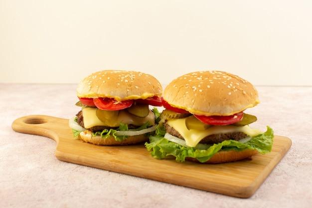 Une vue de face des hamburgers de viande avec légumes et salade verte sur la table en bois