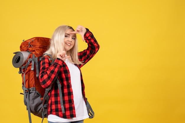 Vue de face happy blonde traveller femme avec son sac à dos faisant signe de l'appareil photo debout sur le mur jaune