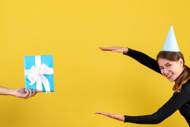 Vue de face happy young girl with party cap essayant de montrer la taille de la boîte cadeau bleu
