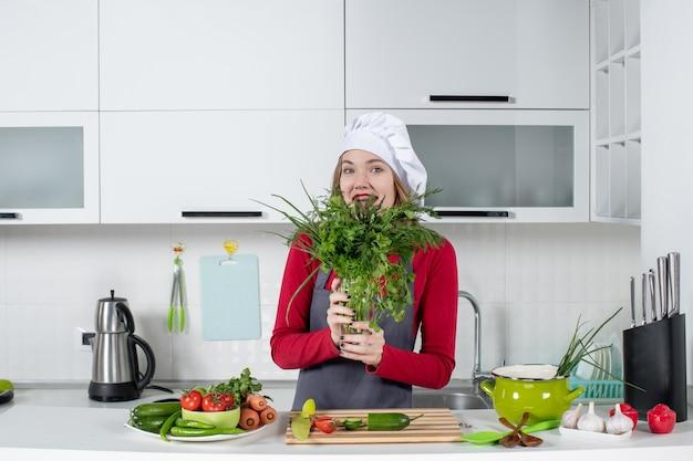 Vue de face heureuse femme chef en chapeau de cuisinier brandissant les verts