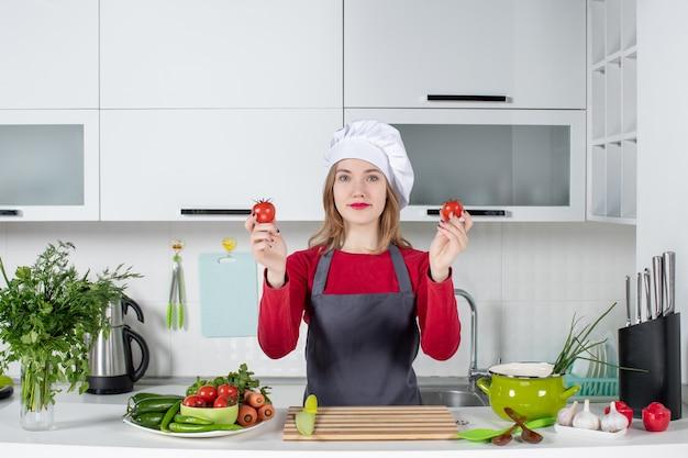Vue de face heureuse femme cuisinier en tablier tenant des tomates