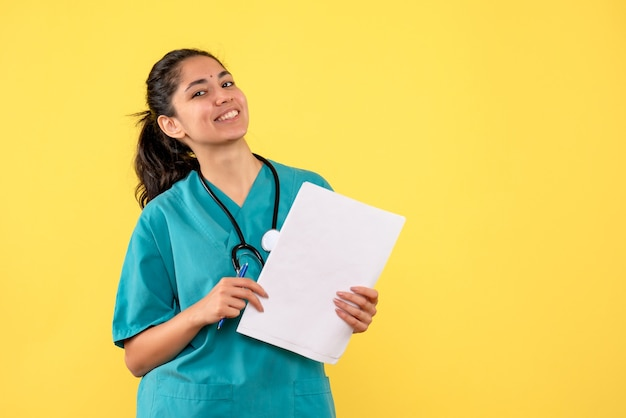 Vue de face heureuse femme médecin avec des documents sur fond jaune