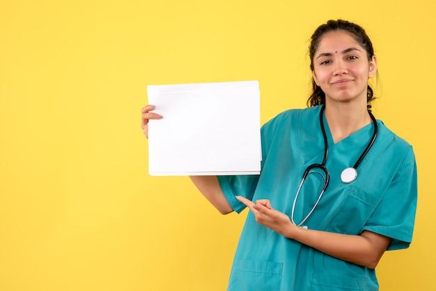 Vue de face heureuse femme médecin pointant sur des papiers sur fond jaune