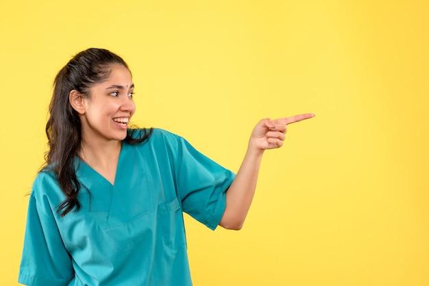 Vue de face heureuse femme médecin en uniforme debout sur fond isolé jaune