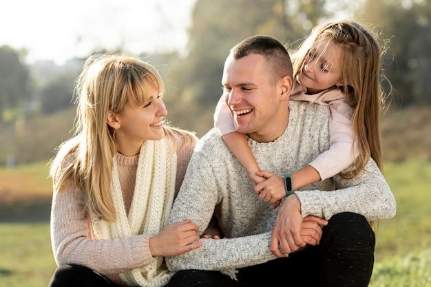 Vue de face heureuse jeune famille se regardant