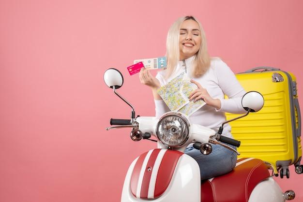 Vue de face heureuse jeune femme sur cyclomoteur tenant un billet de carte et une carte