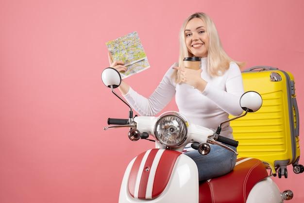 Vue de face heureuse jeune femme sur cyclomoteur avec valise jaune pointant la carte