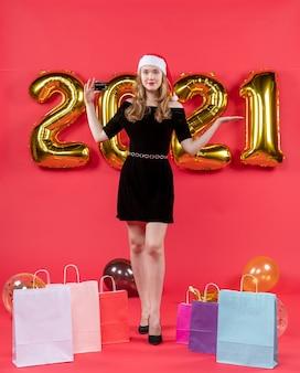 Vue de face heureuse jeune femme dans des sacs de robe noire sur des ballons au sol sur fond rouge