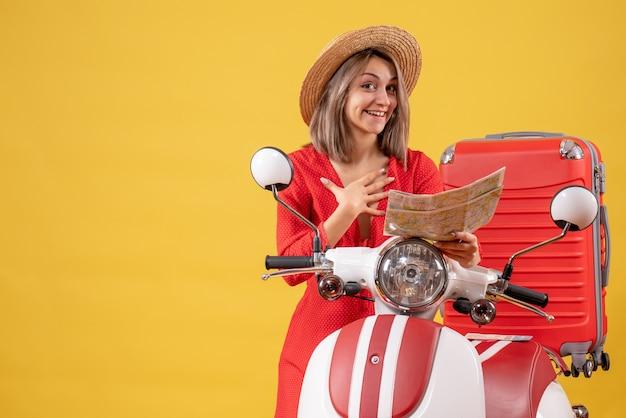 Vue de face de l'heureuse jeune femme en robe rouge près de la carte de tenue de cyclomoteur