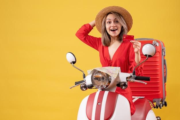 Vue de face de l'heureuse jeune femme en robe rouge tenant une carte bancaire sur un cyclomoteur