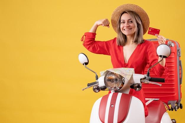 Vue de face de l'heureuse jeune femme en robe rouge tenant une carte de crédit montrant le muscle du bras près de cyclomoteur
