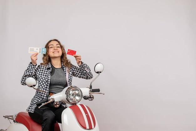 Vue de face de l'heureuse jeune fille sur un cyclomoteur tenant un billet et une carte sur un mur gris