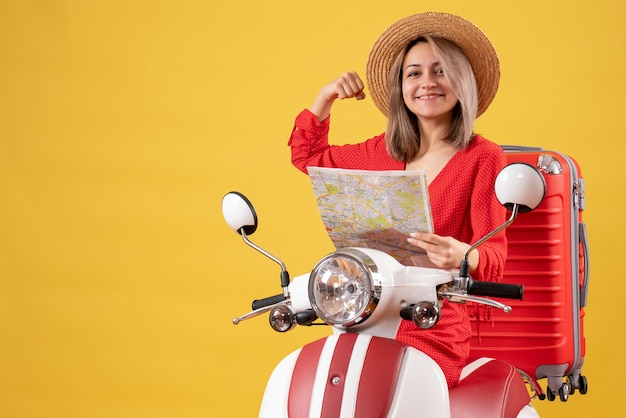 Vue de face de l'heureuse jolie fille sur cyclomoteur avec valise rouge tenant la carte