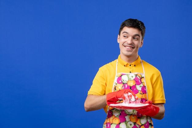 Vue de face heureuse ménagère mâle lave-assiette sur espace bleu