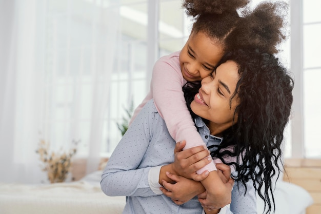Vue de face de l'heureuse mère jouant à la maison avec sa fille