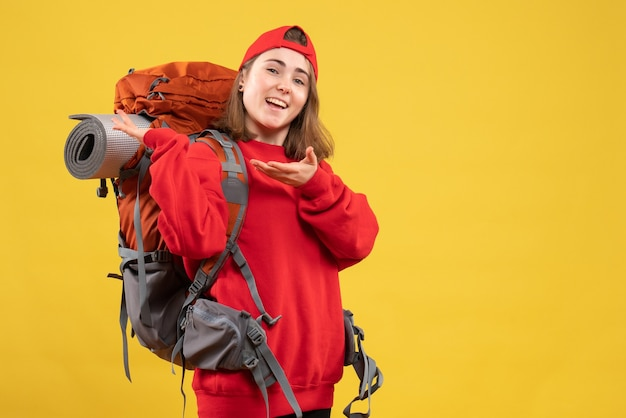 Vue de face heureuse voyageuse avec bonnet rouge pointant sur son sac à dos