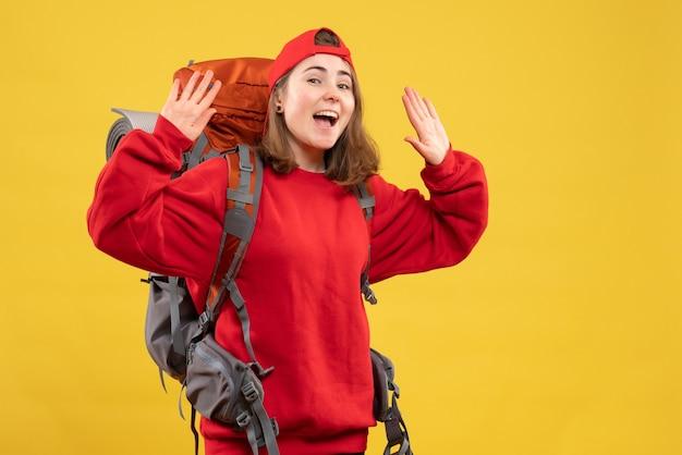 Vue de face heureuse voyageuse avec sac à dos en levant les mains