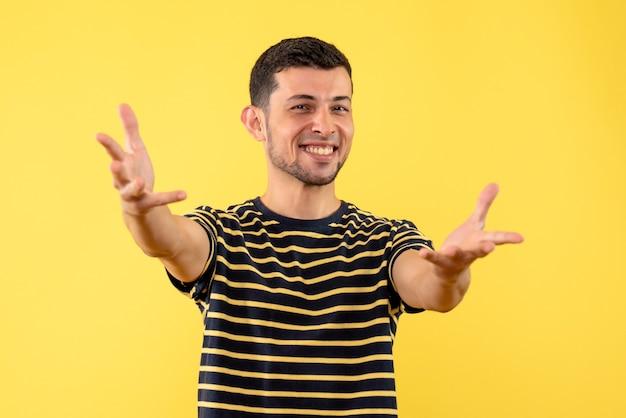 Vue de face heureux bel homme en t-shirt rayé noir et jaune fond isolé jaune
