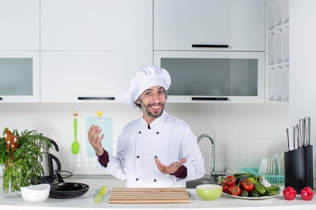 Vue de face heureux chef masculin en chapeau de cuisinier debout derrière la table de la cuisine dans la cuisine