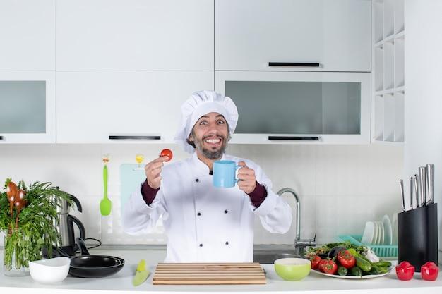 Vue de face heureux chef masculin en chapeau de cuisinier debout derrière la table de la cuisine tenant une tasse et une tomate