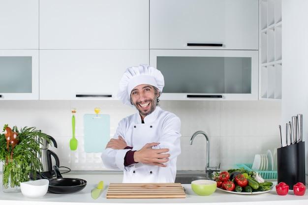 Vue de face heureux chef masculin en chapeau de cuisinier traversant les mains debout derrière la table de la cuisine